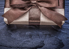 Giftbox with brown satin ribbon on wood board directly above Stock Images