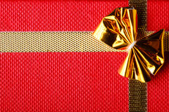 Giftbox closeup. Golden bow on red background Royalty Free Stock Photography