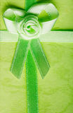 Giftbox closeup. Ribbon with bow on green background Royalty Free Stock Photography