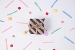 Giftbox con el caramelo del candlesand para el cumpleaños en fondo rosado Foto de archivo
