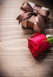 Giftbox con il bocciolo di rosa rosso dell'arco sul concetto di festa del bordo di legno Immagine Stock