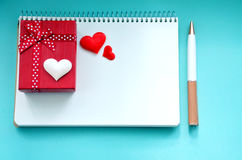 Giftbox, een blocnote, een pen en harten op een blauwe achtergrond Royalty-vrije Stock Afbeeldingen
