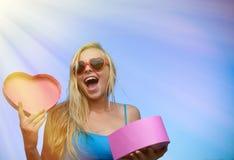 Giftbox en forme de coeur d'ouverture enthousiaste heureuse de fille dessus Images stock
