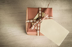 Giftbox with Label Overhead. A single gift box with tied gingham ribbon on a faded old wooden table, photographed from above with blank label facing upwards Royalty Free Stock Photography