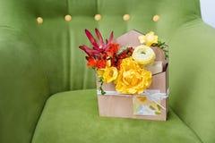 Giftbox mit Blumen und Grußkarte Bunter Frühlingsblumenstrauß in der Holzkiste auf grünem weichem Lehnsessel Lizenzfreie Stockfotografie