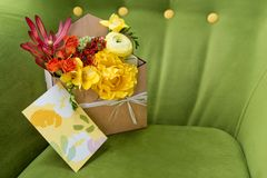 Giftbox mit Blumen und Grußkarte Bunter Frühlingsblumenstrauß in der Holzkiste auf grünem weichem Lehnsessel Stockbild