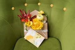 Giftbox mit Blumen und Grußkarte Bunter Frühlingsblumenstrauß in der Holzkiste auf grünem weichem Lehnsessel Lizenzfreie Stockfotos
