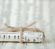 Giftbox on music sheet. A musical gift on notes background.  Stock Photography