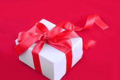 Giftbox with red ribbon Stock Images