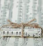 Giftbox sur la feuille de musique Un cadeau musical sur le fond de notes image libre de droits