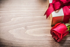 Giftbox with tied bow expanded rose on wooden board copyspace Royalty Free Stock Photo