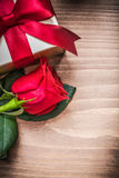 Giftbox with tied bow rose on wooden board top view Stock Images