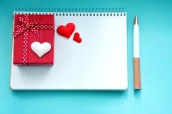 Giftbox, um bloco de notas, pena e corações em um fundo azul Imagens de Stock Royalty Free