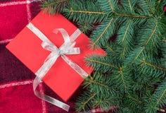 Giftbox vermelho com a fita de prata sob a árvore de Natal imagens de stock royalty free