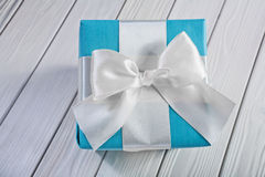 Giftbox with white ribbon and bow on painted boards Royalty Free Stock Photo