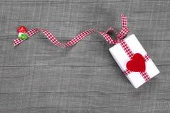Giftbox wickelte im Papier mit einem Rot ein, das auf Holz gehört wurde Stockbild