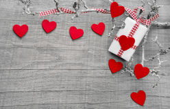 Giftbox wrapped in paper with hearts on a wooden background Royalty Free Stock Images
