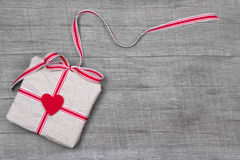 Giftbox wrapped in paper with a red heard on wood Stock Photography