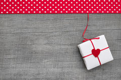 Giftbox wrapped in paper with a red heard on a wooden background. For christmas, valentine, mother's day or wedding - shabby chic style royalty free stock photo