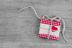 Giftbox wrapped in red paper with red heart for Christmas Stock Images