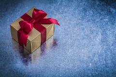 Giftbox wrapped in shining golden paper on metallic surface Royalty Free Stock Image