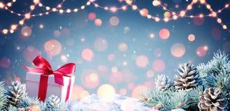 GiftBox y ramas del abeto en nieve imágenes de archivo libres de regalías