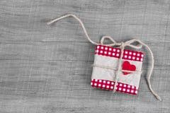 Giftbox zawijał w czerwień papierze z czerwonym sercem dla bożych narodzeń Obrazy Stock