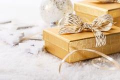 Giftboxes brillantes con los arcos en nieve Imágenes de archivo libres de regalías