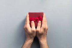 Giftboxes de los días de fiesta en manos del hombre en el fondo azul en colores pastel FO Fotografía de archivo