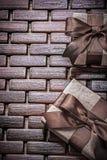 Giftboxes envolvió con las cintas marrones en los días de fiesta de madera de la estera concentrados fotos de archivo