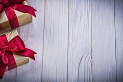 Giftboxes envueltos con los arcos atados en holid del copyspace del tablero de madera fotos de archivo libres de regalías