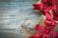 Giftboxes in glittery wrapping paper on vintage wooden board hol Royalty Free Stock Photos