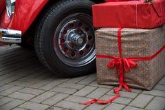 Giftboxes lögn på jordning bredvid den röda retro bilen royaltyfri bild