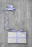 Giftboxes mit blauem gestreiftem Band auf einem hölzernen Hintergrund Lizenzfreie Stockfotos