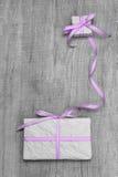 Giftboxes mit purpurrotem gestreiftem Band auf einem grauen hölzernen backround Lizenzfreies Stockfoto