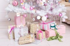 Giftboxes, pink and white christmas decorations balls hanging on Stock Photos