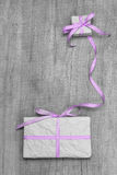 Giftboxes with purple striped ribbon on a grey wooden backround Royalty Free Stock Photo