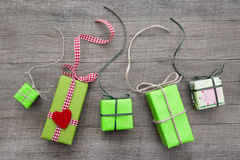 Giftboxes wrapped in different kinds of green paper with wood Royalty Free Stock Photography