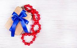 Giftdoos met blauwe boog en rode koraalparels op een witte houten achtergrond Verrassing aan de vrouw Stock Foto