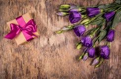Giftdoos met boog en purpere bloemen Eustoma Een romantische gift De dag van moeders Stock Foto