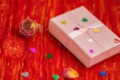 Giftdoos met decoratieve harten op een rode achtergrond Stock Foto's