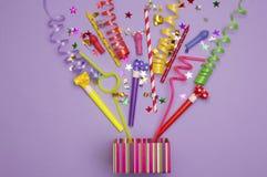 Giftdoos met diverse partijconfettien, ballons, wimpels, noisemakers en decoratie op een groene achtergrond kleurrijk royalty-vrije stock afbeelding