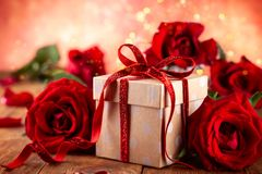 Giftdoos met rode lintboog en rode rozen stock afbeelding