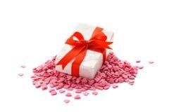 Giftdoos met rood lint die op een stapel van hart gevormd suikergoed liggen stock foto