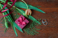Giftdoos met tulpen en kruiden en verlovingsringen op hout wa Stock Fotografie