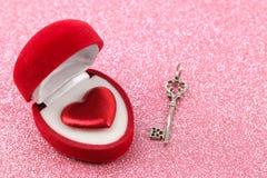 Giftdoos met zeer belangrijk en rood hartenclose-up op een heldere glanzende roze achtergrond De dag van de valentijnskaart `s stock foto's