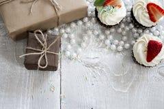 Giftdozen en Chocolade cupcake met witte room en aardbei Royalty-vrije Stock Afbeelding