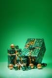 Giftdozen en Kerstmisballen, op groene achtergrond worden geïsoleerd die Royalty-vrije Stock Afbeeldingen