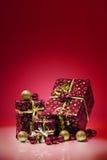 Giftdozen en Kerstmisballen, op rode achtergrond worden geïsoleerd die Royalty-vrije Stock Afbeeldingen