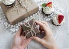 Giftdozen in vrouwenhand en Chocolade cupcake met witte room Royalty-vrije Stock Foto's
